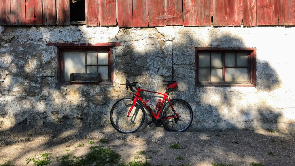 Photo of my bike against a red barn, my attempt at an artistic photo, inspired by GravelRoad.Ca's instagram account.