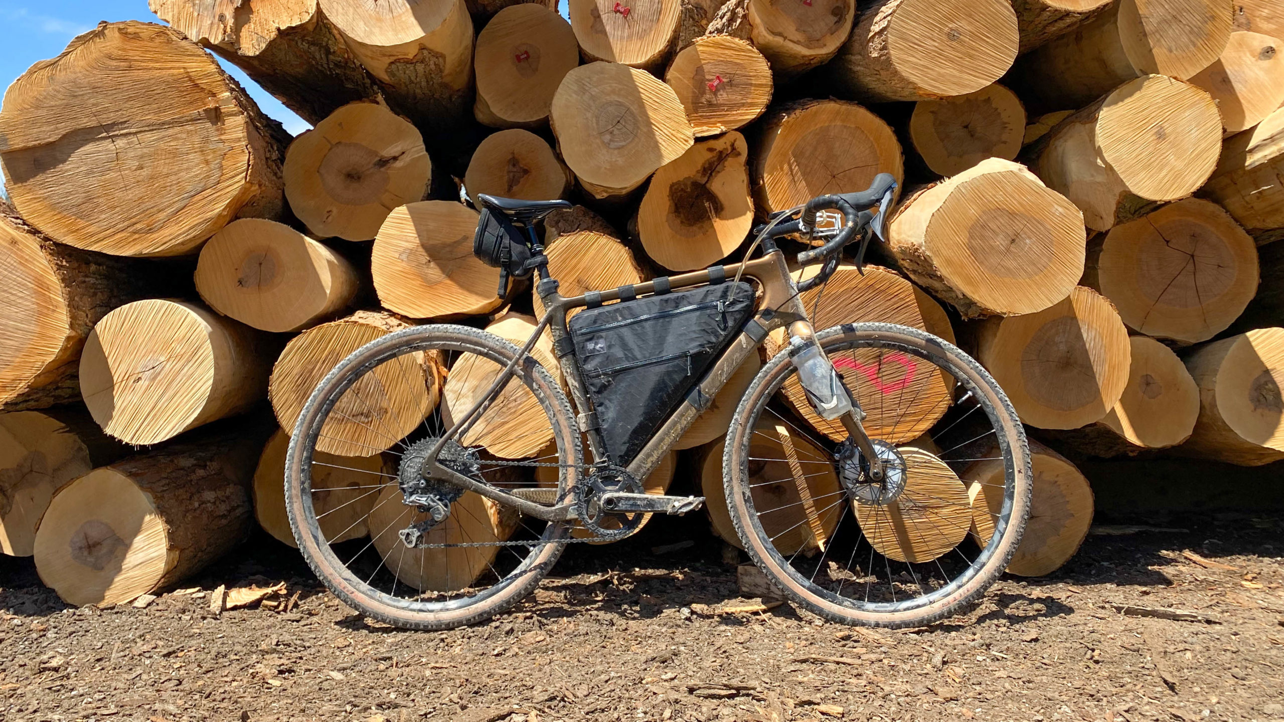 Field and Forest Frame Bag on my Norco Search packed in front of a pile of freshly cut logs.